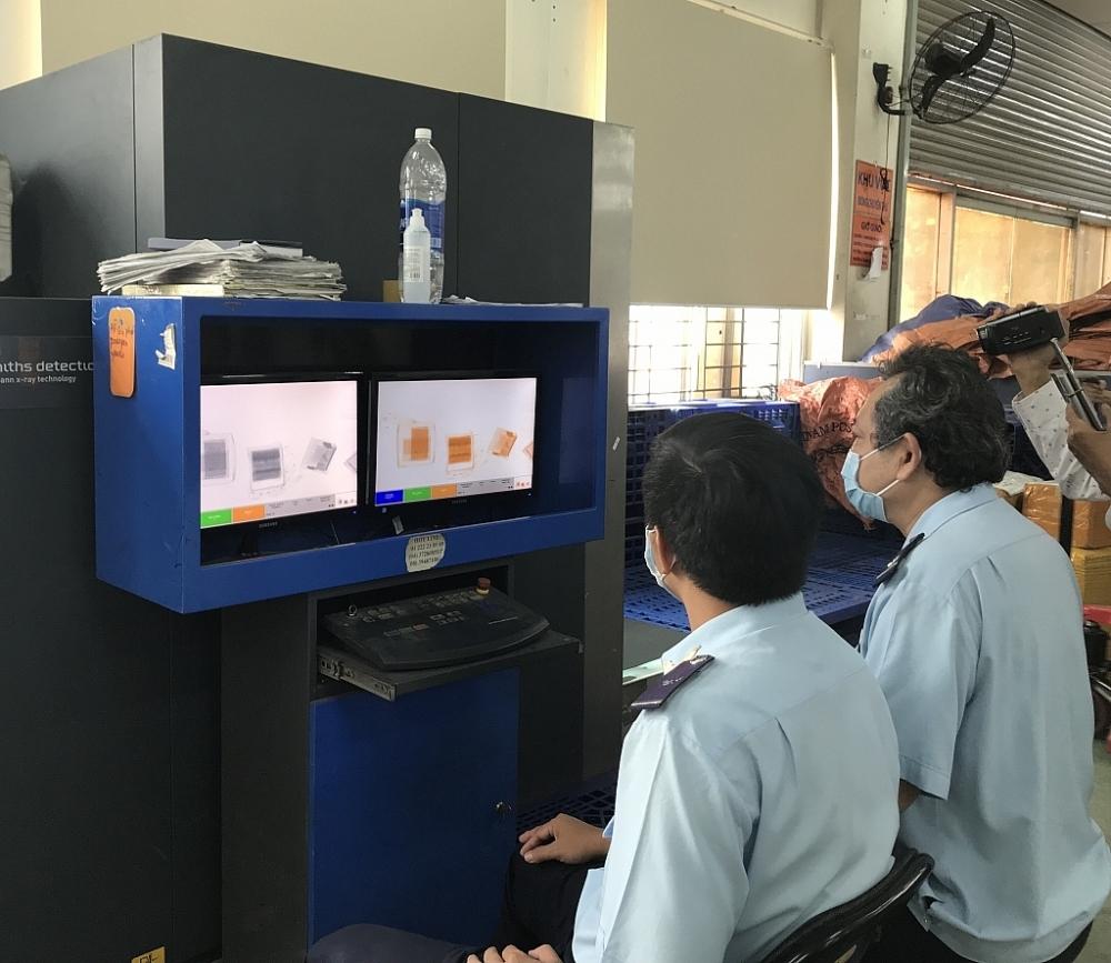 Công chức Hải quan Chuyển phát nhanh kiểm tra hàng hóa NK qua máy soi. Ảnh: T.H