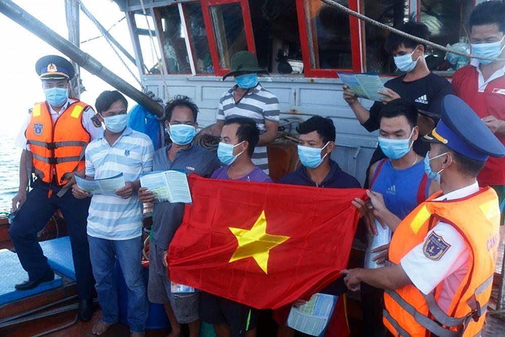 Lực lượng Cảnh sát biển tặng cờ và phát tờ rơi tuyên truyền Luật Cảnh sát biển Việt Nam cho bà con ngư dân đi biển. Ảnh: Phạm Doanh
