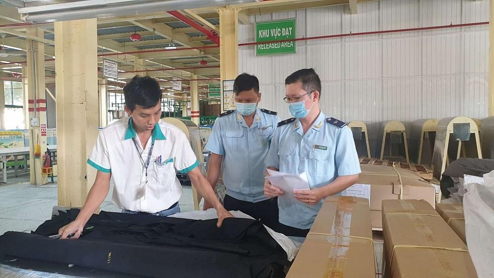 Công chức Chi cục Hải quan cửa khẩu Vĩnh Long (Cục Hải quan Cần Thơ) kiểm tra thực tế nguyên liệu nhập khẩu. Ảnh: Đăng Nguyên