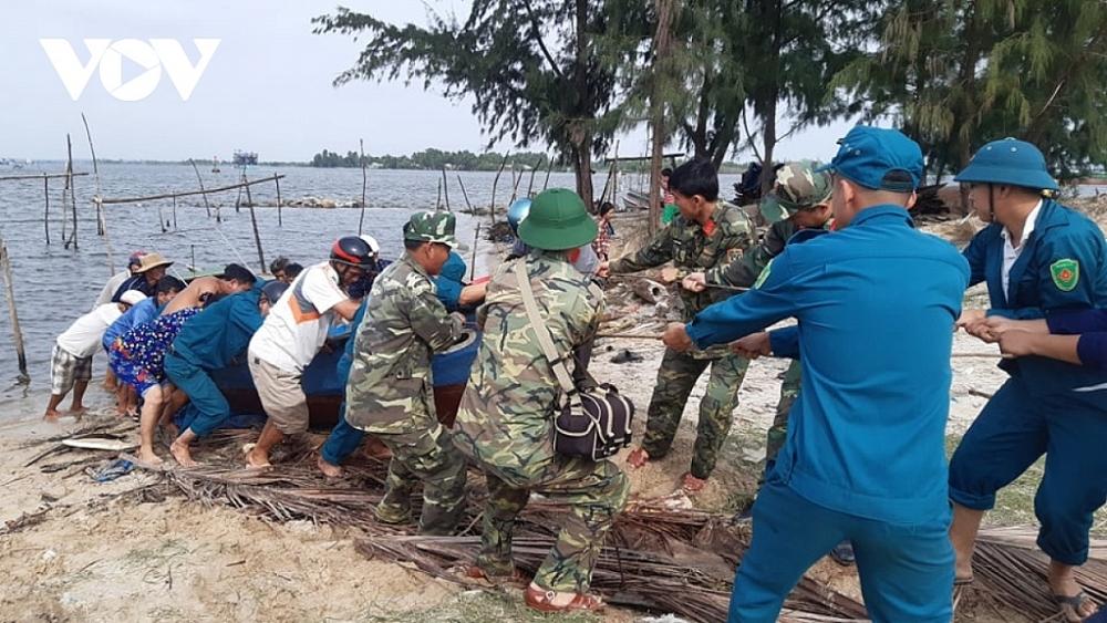 Các lực lượng chức năng ở Quảng Nam hỗ trợ người dân đưa thuyền lên bờ tránh bão. Ảnh: VOV