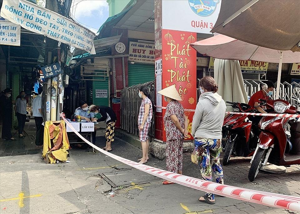 Người dân xếp hàng, khai báo y tế khi vào chợ Vườn Chuối (quận 3, TPHCM). Ảnh
