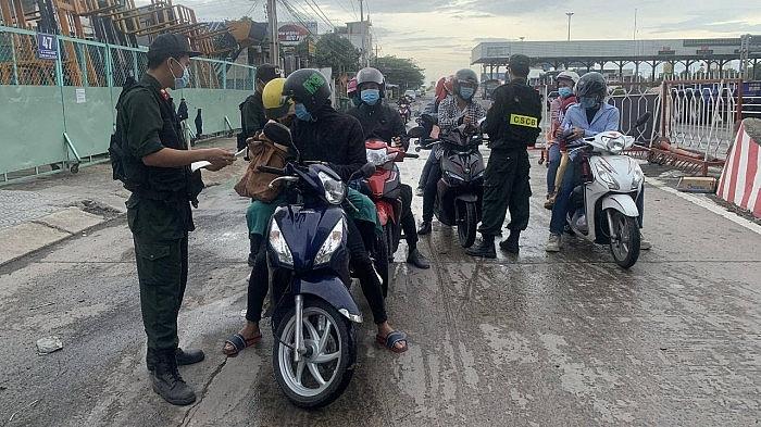 Người dân đi xe máy về quê qua chốt kiểm dịch QL1 gần cầu Đồng Nai chiều 28/7/2021. Ảnh Đỗ Loan