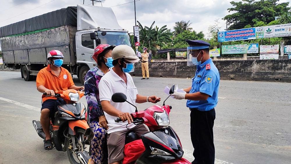 Lực lượng chức năng Long An kiểm tra giấy đi đường của người dân khi tham gia lưu thông. Ảnh CTV