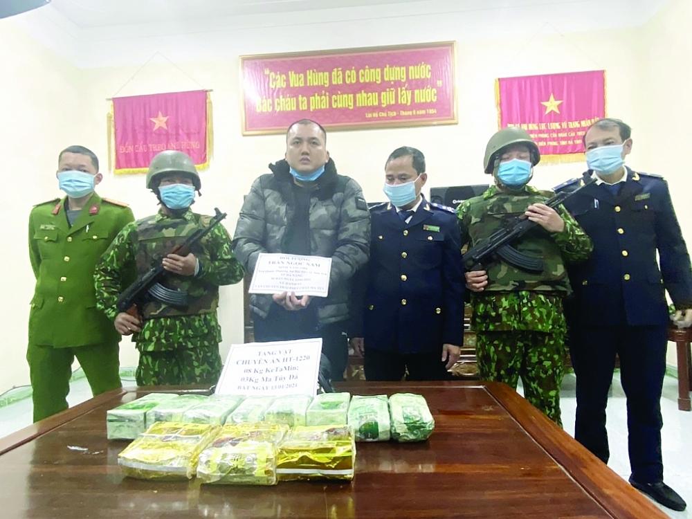 Đối tượng Trần Ngọc Nam (cầm giấy ) cùng tang vật khi bị bắt giữ. Ảnh: Phong Lê