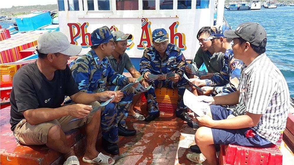 Lực lượng Cảnh sát biển phát tờ rơi, tuyên truyền chính sách biển đảo cho ngư dân. Ảnh: Đ.Thịnh