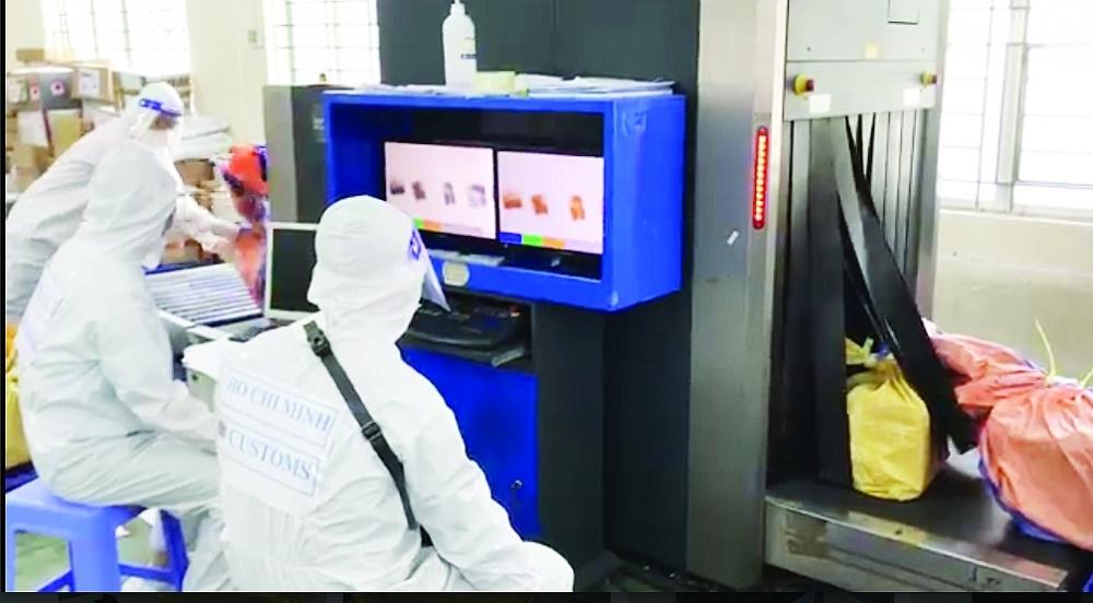 Công chức Hải quan Chuyển phát nhanh - Cục Hải quan TPHCM kiểm tra các kiện hàng qua máy soi. Ảnh: T.H