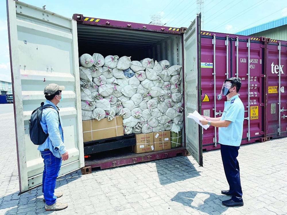 Công chức Chi cục Hải quan cảng Sài Gòn khu vực 1 làm thủ tục thông quan hàng hóa cho DN. Ảnh: T.H