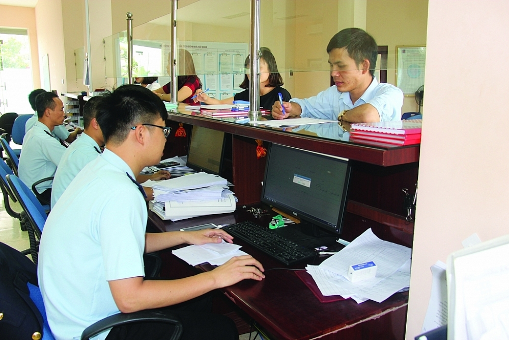 Công chức Hải quan Hà Nam (Cục Hải quan Hà Nam Ninh) hướng dẫn DN làm thủ tục hải quan. Ảnh: H.Nụ