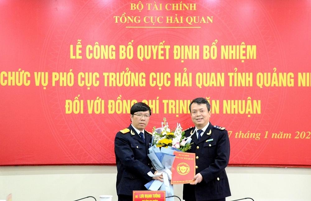 Phó Tổng cục trưởng Tổng cục Hải quan Lưu Mạnh Tưởng (bên trái) tăng hoa chúc mừng và trao quyết định bổ nhiệm cho ông Trịnh Văn Nhuận.
