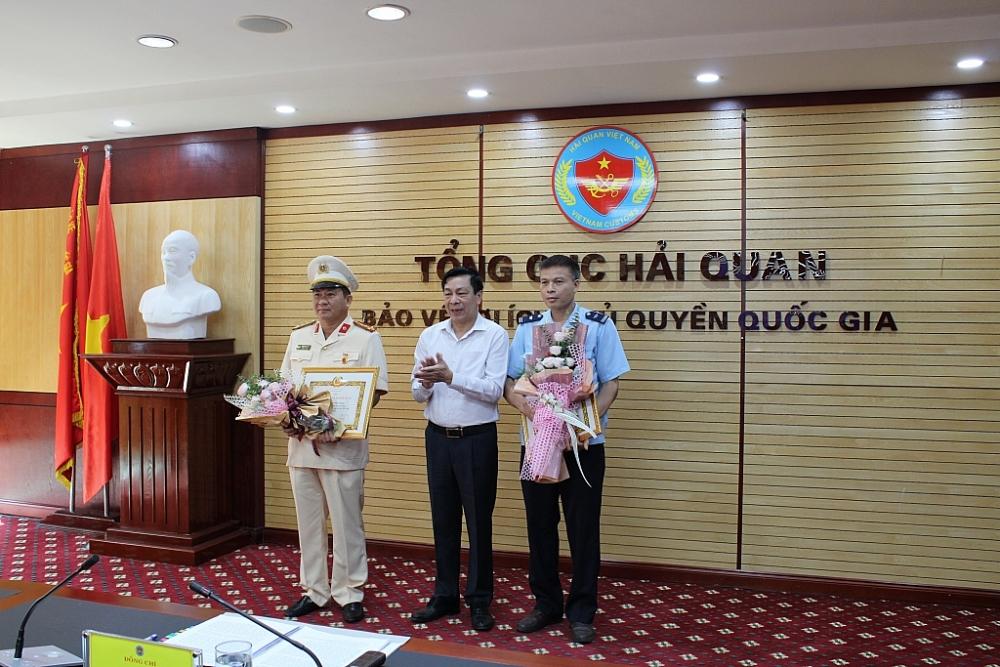 Phó Bí thư thường trực Đảng ủy Bộ Tài chính trao huy hiệu 30 năm tuổi Đảng cho 2 đảng viên. Ảnh: Q.H