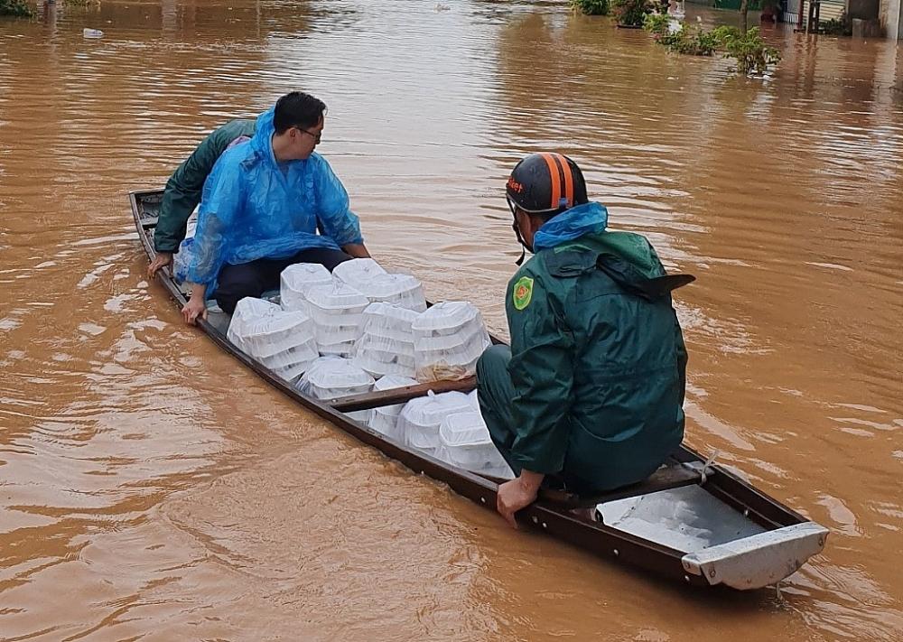 Các đoàn viên di chuyển bằng thuyền để tiếp cận các hộ gia đình bị mưa lũ cô lập.