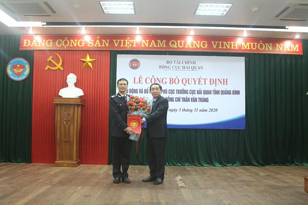 Phó Tổng cục trưởng Tổng cục Hải quan Hoàng Việt Cường tặng hoa chúc mừng và trao quyết định cho ông Trần Văn Tráng. Ảnh: Minh Hồng