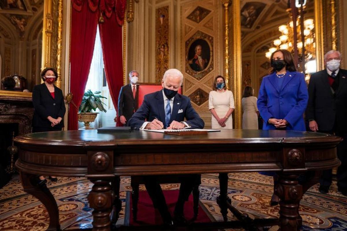 Tổng thống Joe Biden đặt bút ký 3 văn kiện đầu tiên trên cương vị người đứng đầu Nhà Trắng, bao gồm Tuyên bố trong Ngày nhậm chức, Quyết định đề cử các vị trí trong nội các, và Quyết định đề cử các vị trí phụ trong nội các. Ảnh: Reuters