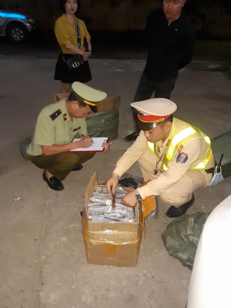 Lực lượng chức năng kiểm tra số hàng vi phạm. Ảnh: QLTT LS