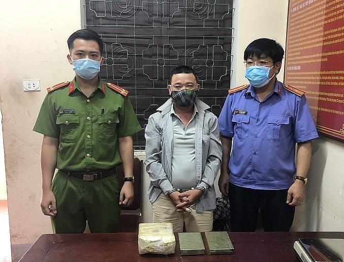 Đối tượng (đứng giữa) cùng tang vật khi bị bắt giữ. Ảnh: CA NA