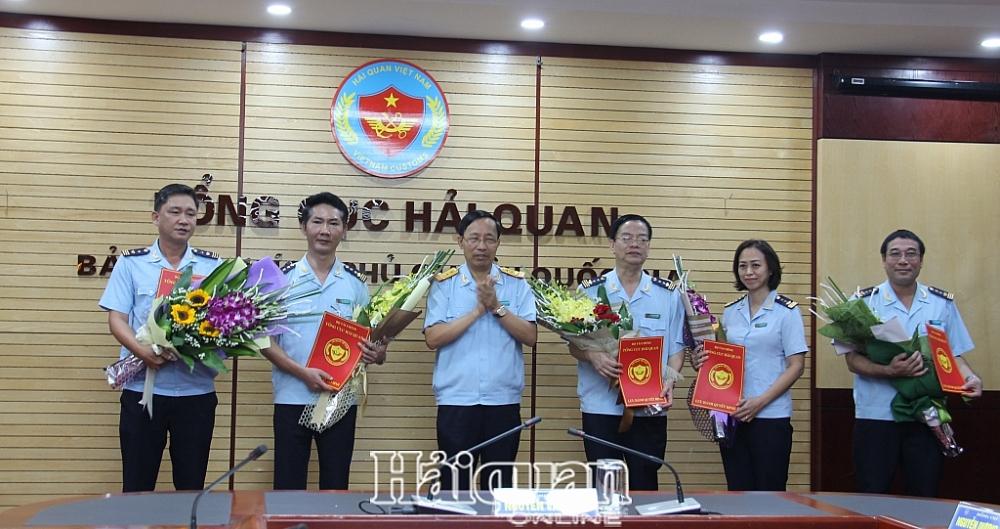 Tổng cục trưởng Nguyễn Văn Cẩn trao quyết định và tặng hoa cho các cá nhân. Ảnh: H.Nụ