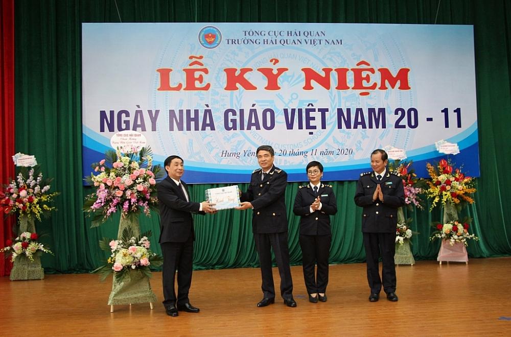 Phó Tổng cục trưởng Hoàng Việt Cường tặng hoa chúc mừng nhà trường. Ảnh: Ngô Dũng