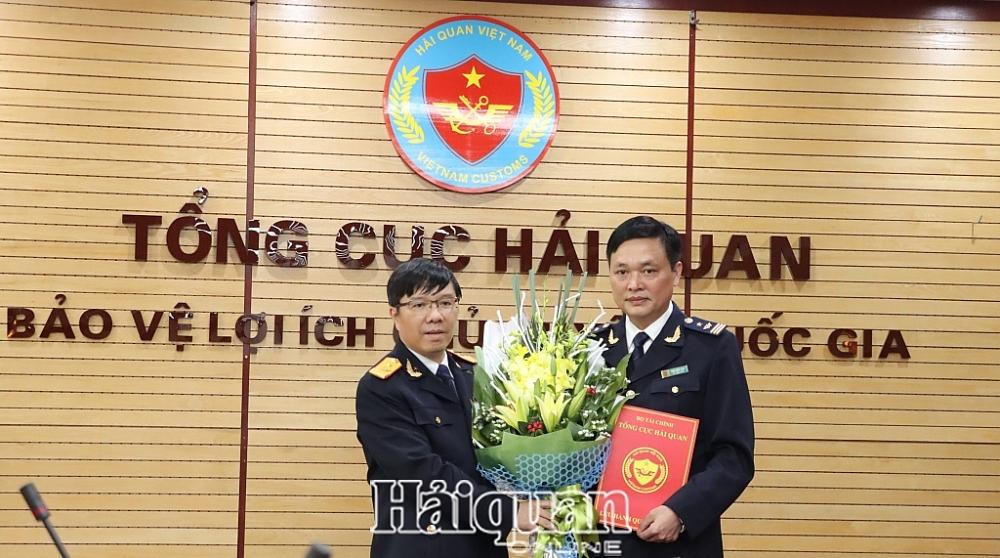 Phó Tổng cục trưởng Lưu Mạnh Tưởng tra quyết định và tặng hoa cho tân Phó Cục trưởng Cục Thuế XNK. Ảnh: H.Nụ