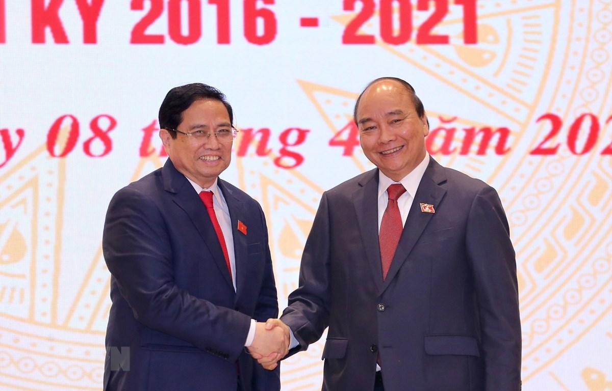 Chủ tịch nước Nguyễn Xuân Phúc, nguyên Thủ tướng Chính phủ chúc mừng Thủ tướng Chính phủ Phạm Minh Chính. (Ảnh: TTXVN)